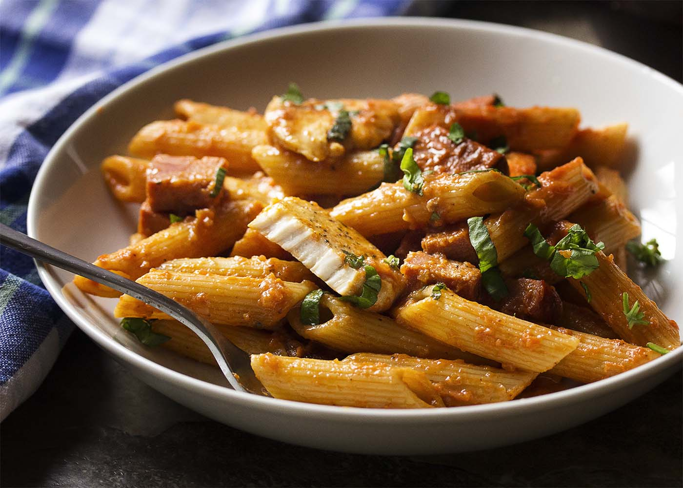 A bowl of penne alla vodka with a glass of wine in the background showing a cut open slice of chicken.