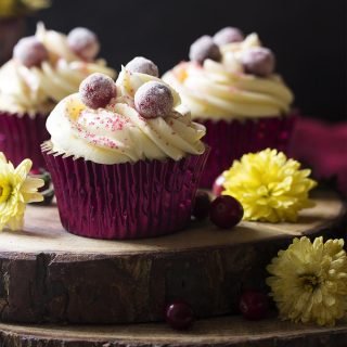 Tender vanilla cake is filled with fresh cranberries and orange zest, then topped with cream cheese frosting in these cranberry orange cupcakes. Great for Thanksgiving or Christmass dessert!   justalittlebitofbacon.com