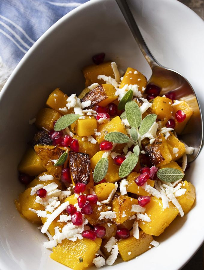Winter squash, ricotta salata, and pomegranate seeds combine to make a warm roasted butternut squash salad which is perfect for fall. Great for the Thanksgiving and holiday table! Healthy. Gluten-Free. | justalittlebitofbacon.com