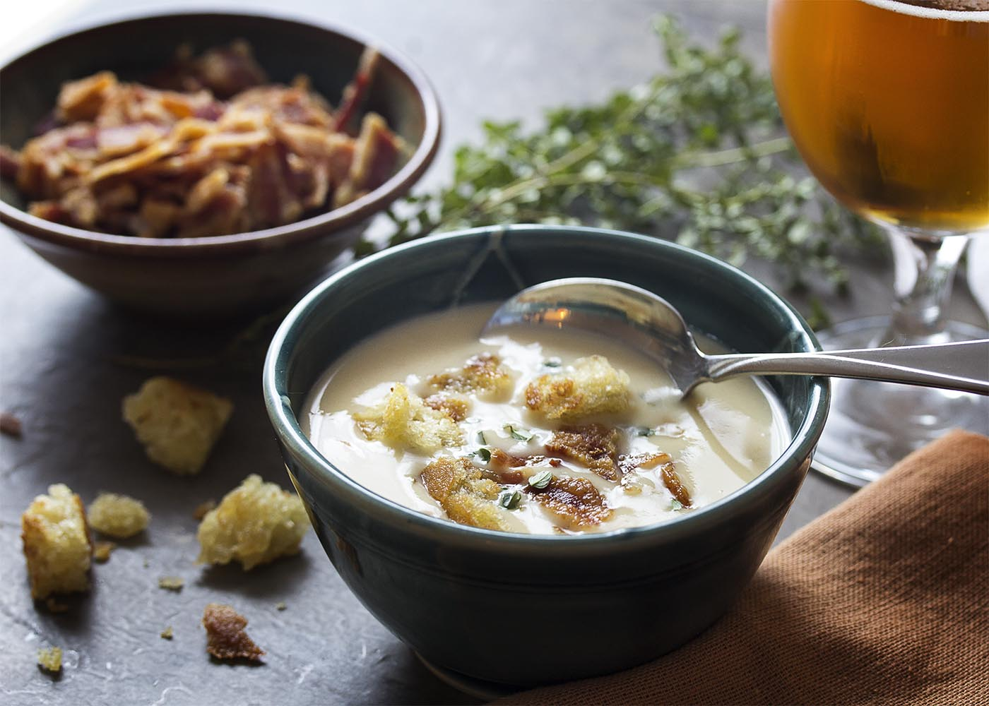 A spoon dipping into a bowl of bacon cheddar soup with croutons and bacon crumbles and a glass of beer.