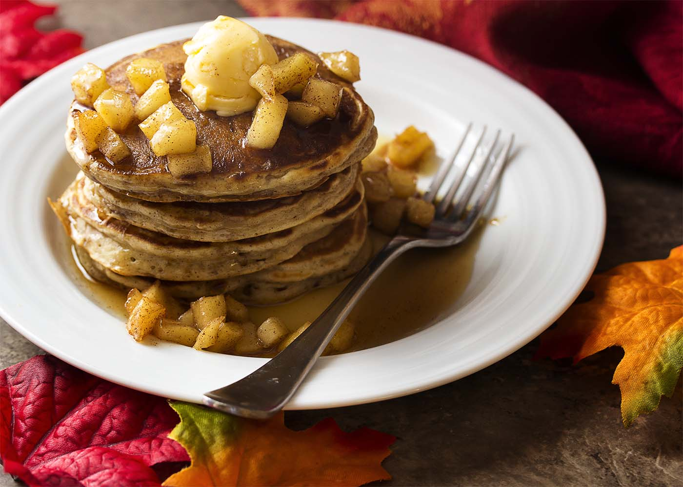 My favorite sour cream pancake batter is mixed with sauteed spiced apples in these apple cinnamon pancakes for the perfect fall and winter breakfast. | justalittlebitofbacon.com