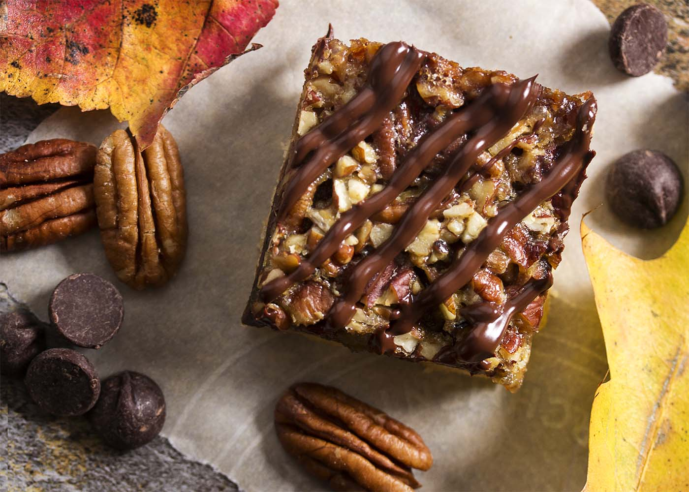 Top view of a chocolate bourbon pecan bar with chocolate drizzle over the top.
