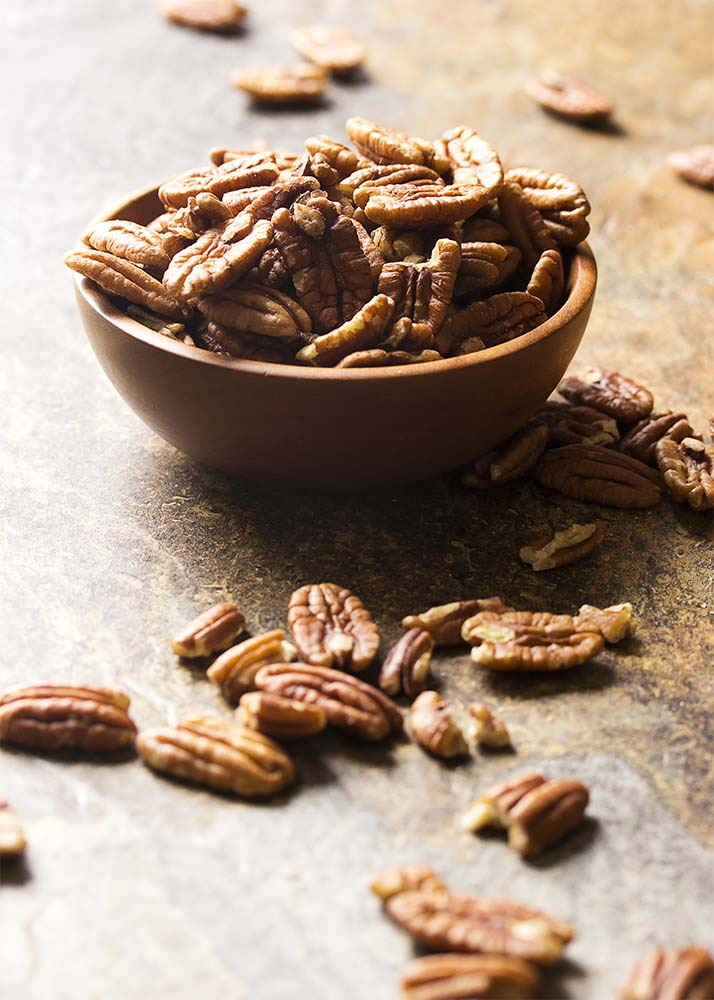 A small wooden bowl filled with pecans with more scattered about.