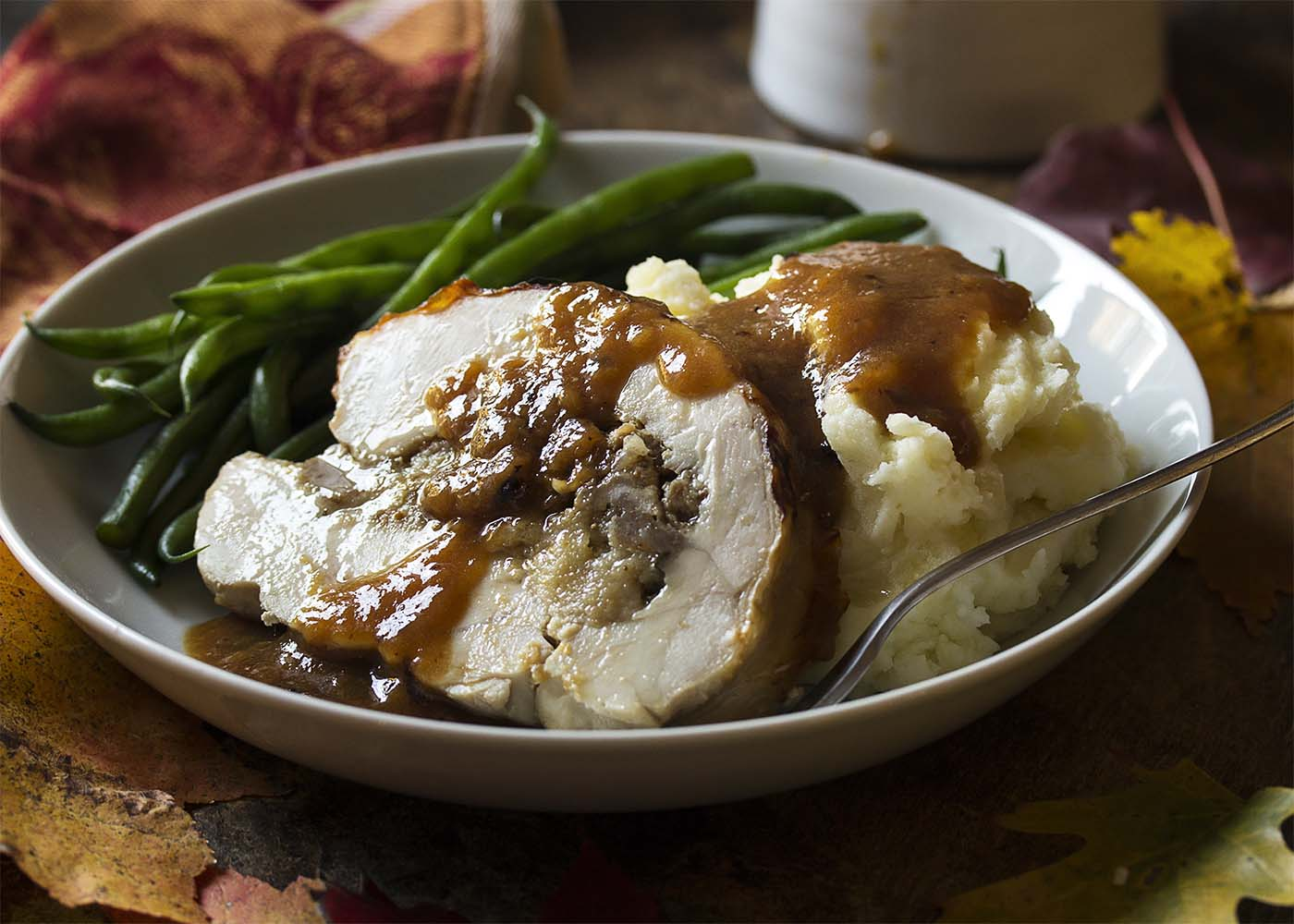 A plate with a slice of turkey breast roulade, mashed potatoes, green beans, and gravy.