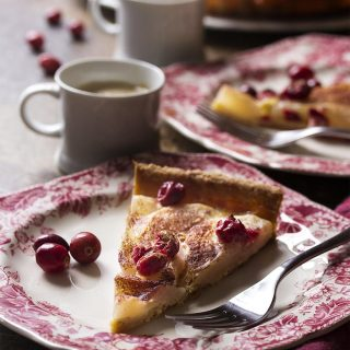 Ripe slices of pears and deep red cranberries combine with a simple custard and a dusting of cinnamon in this pear cranberry tart. Great for the holidays! | justalittlebitofbacon.com