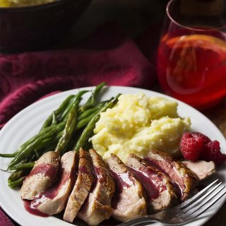 Pan seared duck breast cooked until the skin is golden brown and crispy and then topped with a sweet and spicy make ahead sauce of red wine, port, raspberries, and a little bit of honey. Great for date night, dinner parties, or a romantic Valentine's day meal.