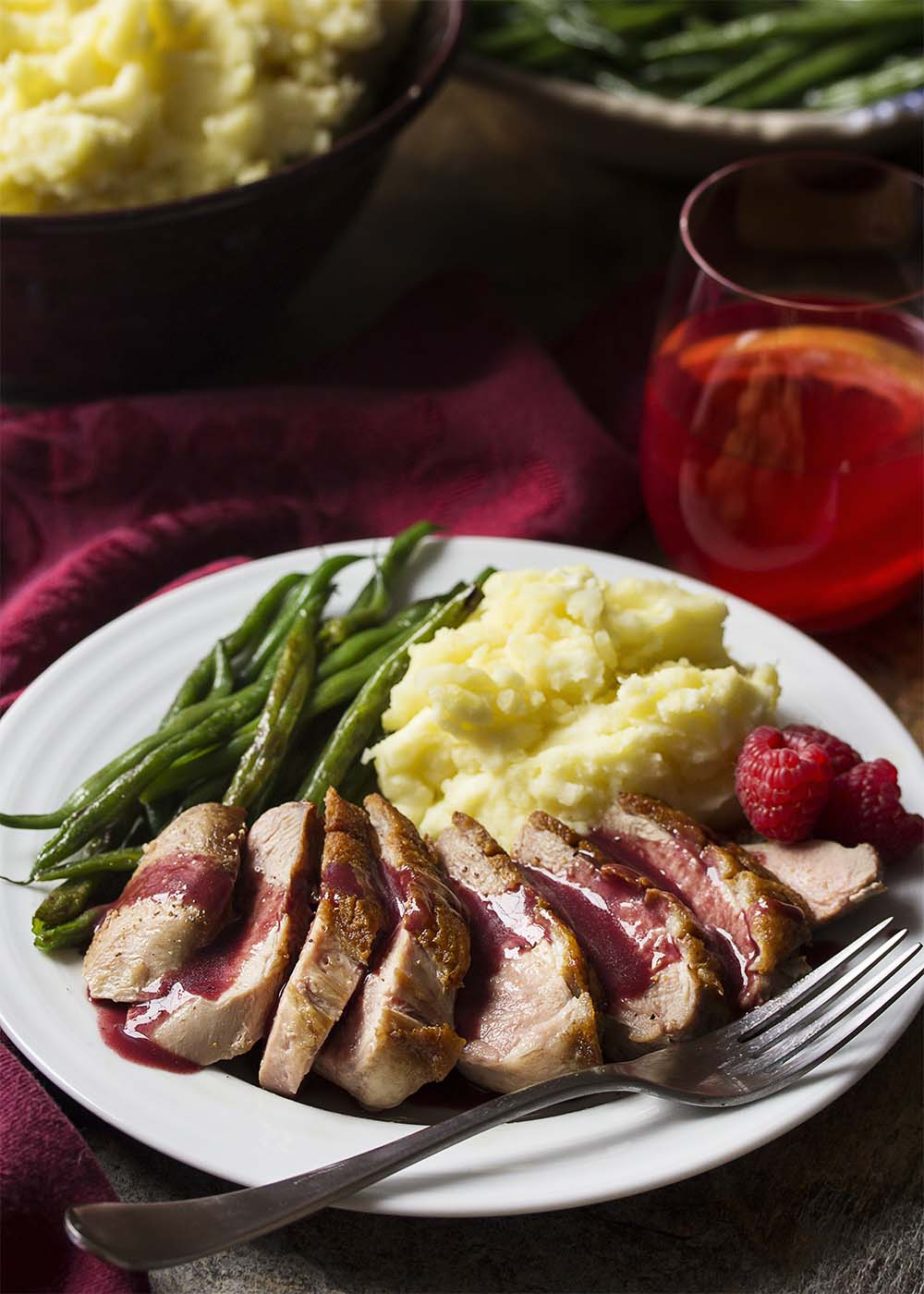 Sliced pan seared duck breast on a plate with raspberry sauce
