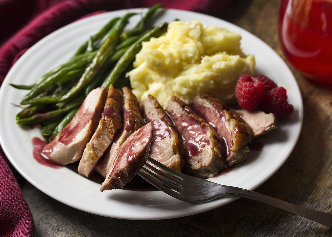 Sliced duck breast on a plate covered with raspberry sauce with a fork lifting a piece