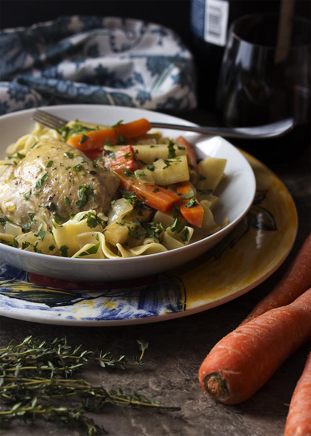 French chicken fricassee in a bowl with root vegetables over a bed of egg noodles.