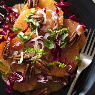 Looking for a healthy and fresh winter salad? Try an Italian orange salad full of sliced cara cara oranges, bitter radicchio, and toasted pecans all tossed with a lemony honey mustard dressing. | justalittlebitofbacon.com