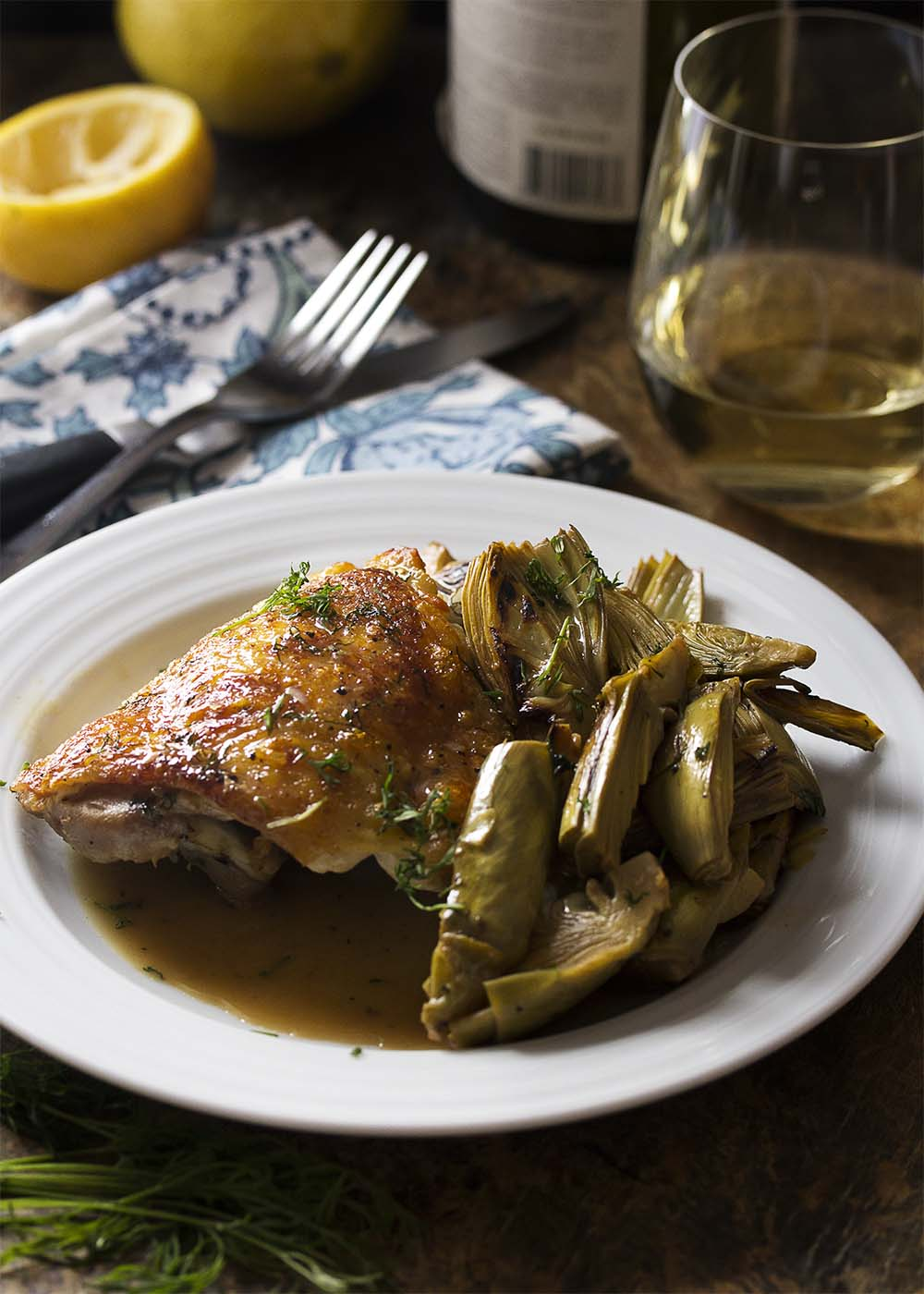 Pan roasted chicken thighs with artichokes on a plate