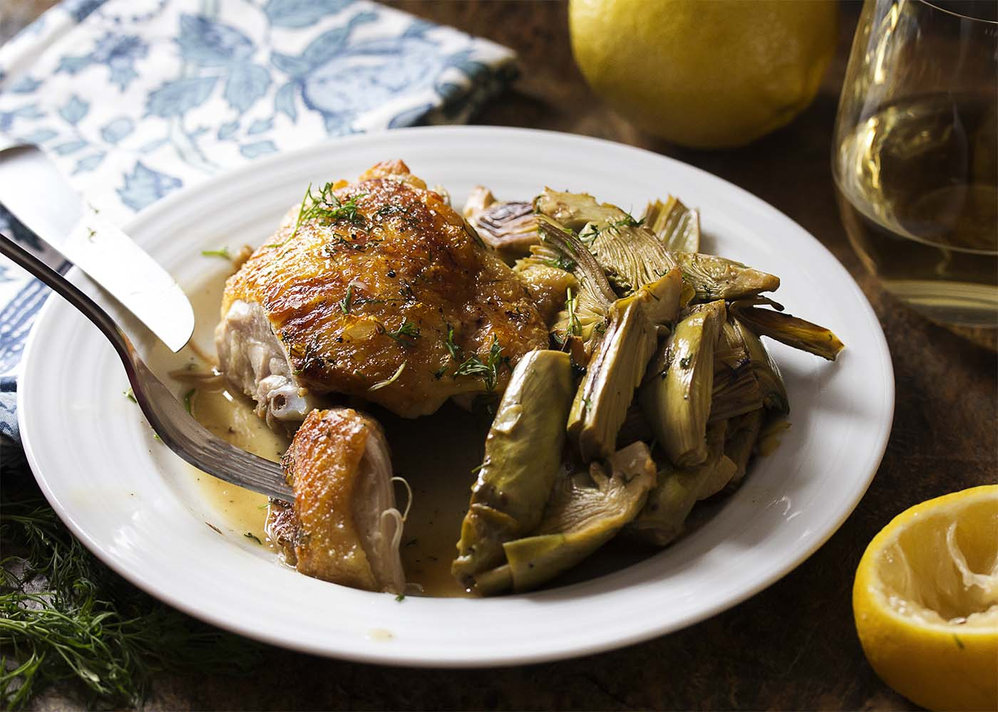 Sliced Mediterranean chicken thigh with artichokes on a plate