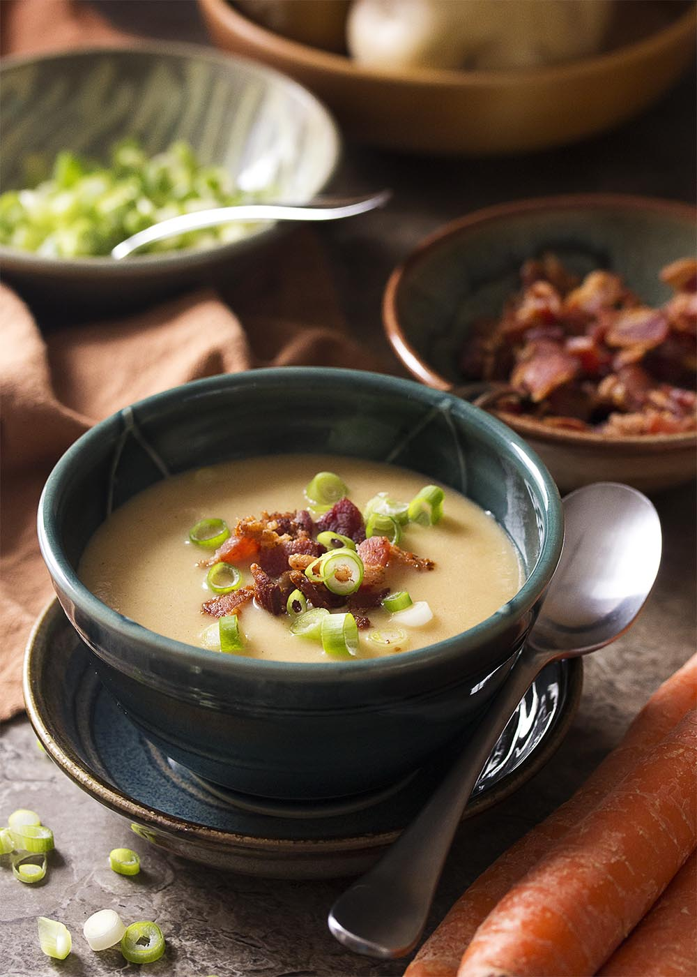 A green bowl of smooth potato carrot soup topped with crispy bacon and sliced scallions.