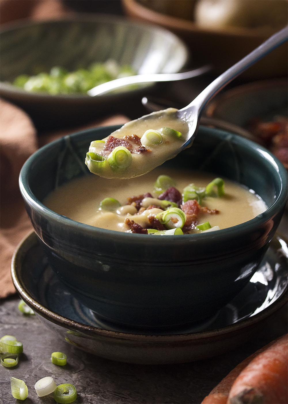 A spoonful of potato carrot soup coming out of the bowl, topped with bacon and scallions.