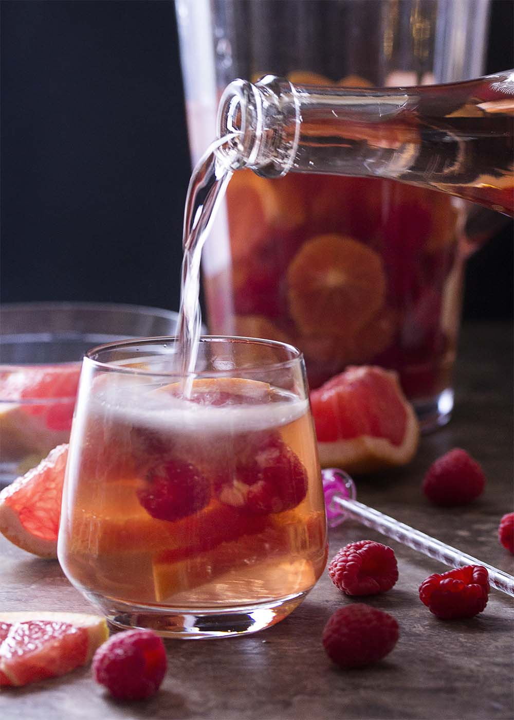 Pouring the sparkling wine into a glass of rose sangria