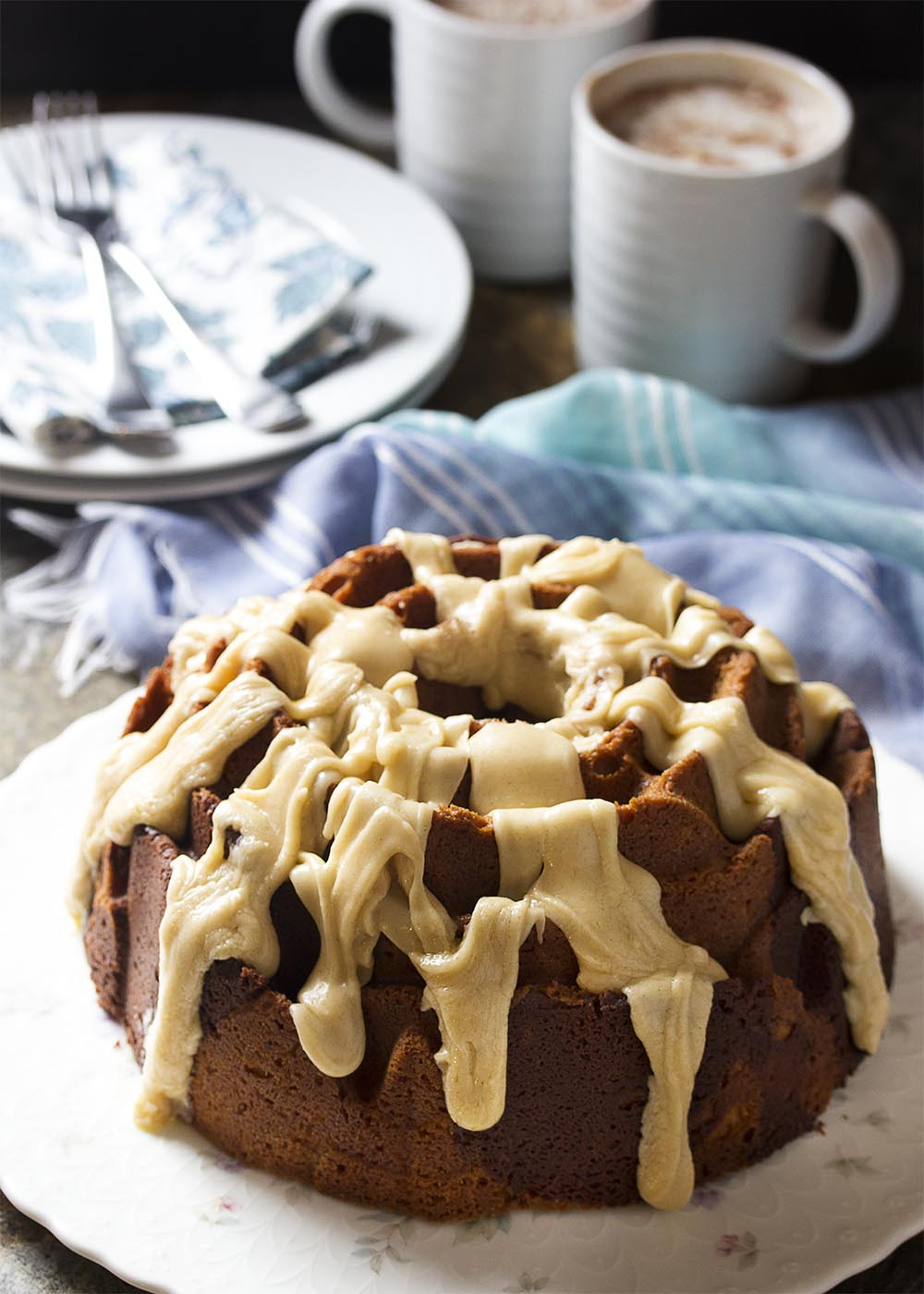 A rose shape cinnamon bundt cake covered with icing sits on a flowered cake platter.