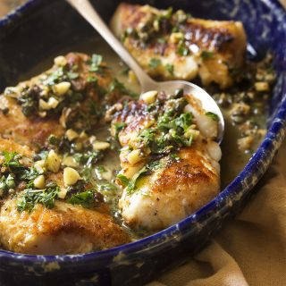 Thick cut cod is pan seared in a mixture of olive oil and butter to produce a golden brown crust and then served with a lemon, parsley, and caper sauce to make a simple and healthy weeknight meal.