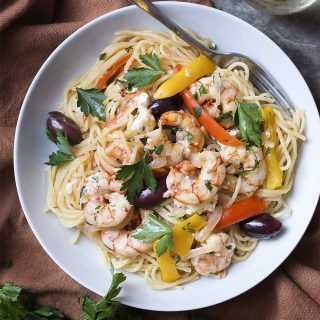 Greek pasta with shrimp, feta, olives is a great and easy skillet dinner full of tender shrimp, salty feta and olives, a good glug of olive oil, and plenty of garlic. And you get to flambe! What could be better?