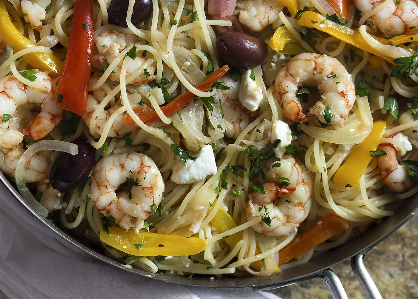 Top down view of the shrimp and pasta in a large saute pan.