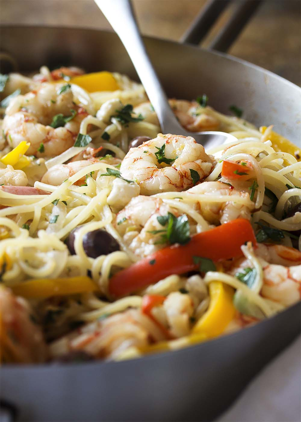 Close-up of a spoon serving a portion of shrimp and pasta from a large saute pan.