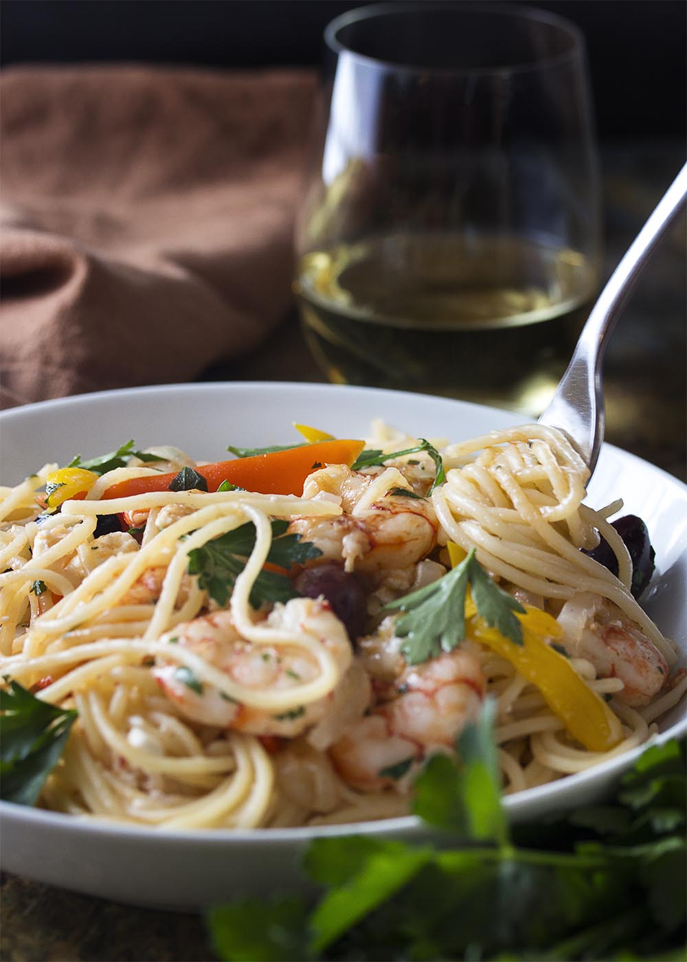 A fork twirling pasta in a white bowl full of Greek shrimp with pasta.