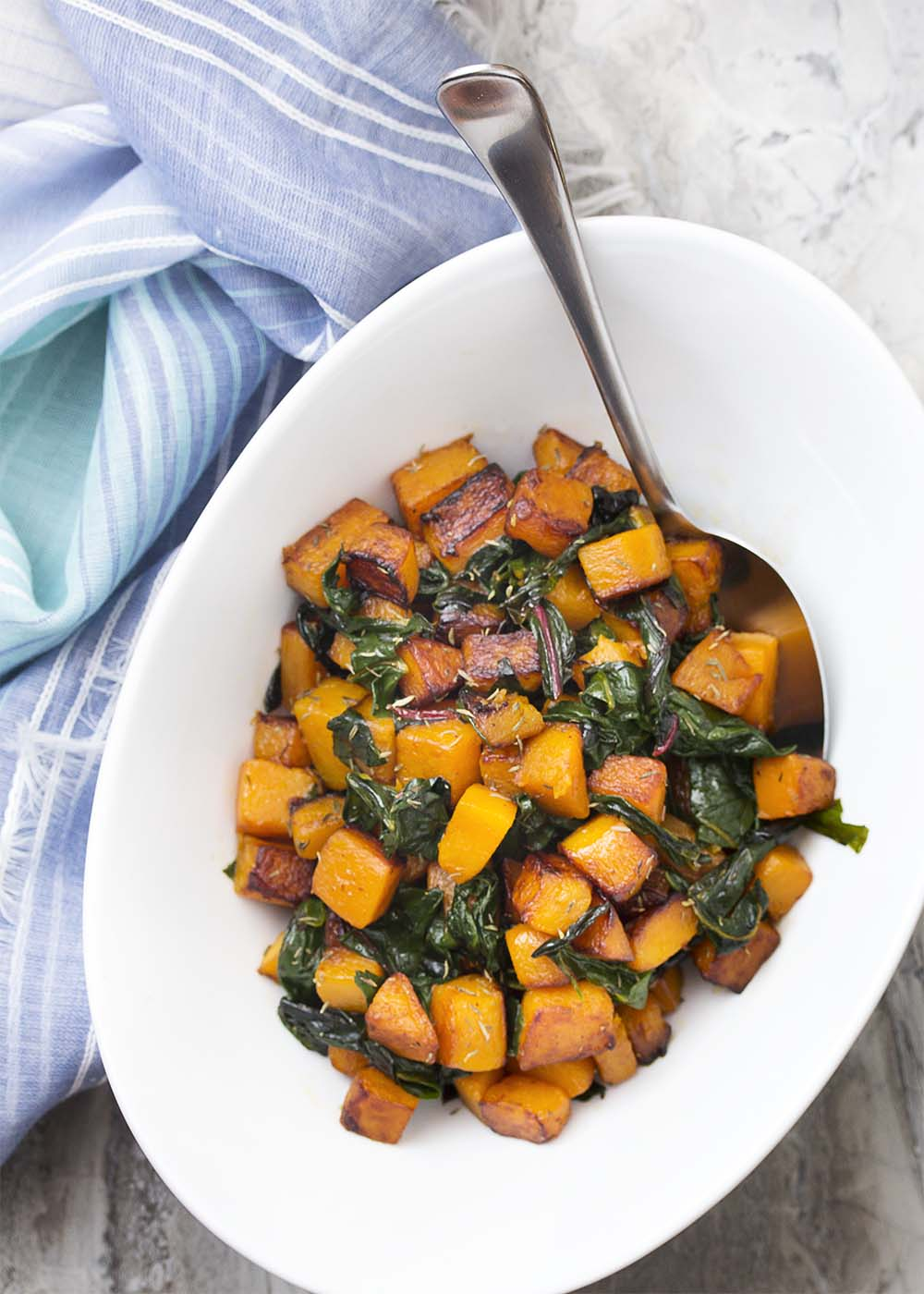Top view of the sauteed squash and chard in a white serving bowl.