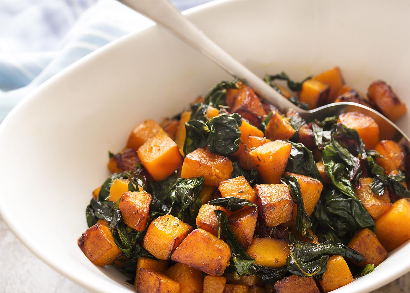 Close up of the sauteed butternut squash cubes and Swiss chard in a white serving bowl