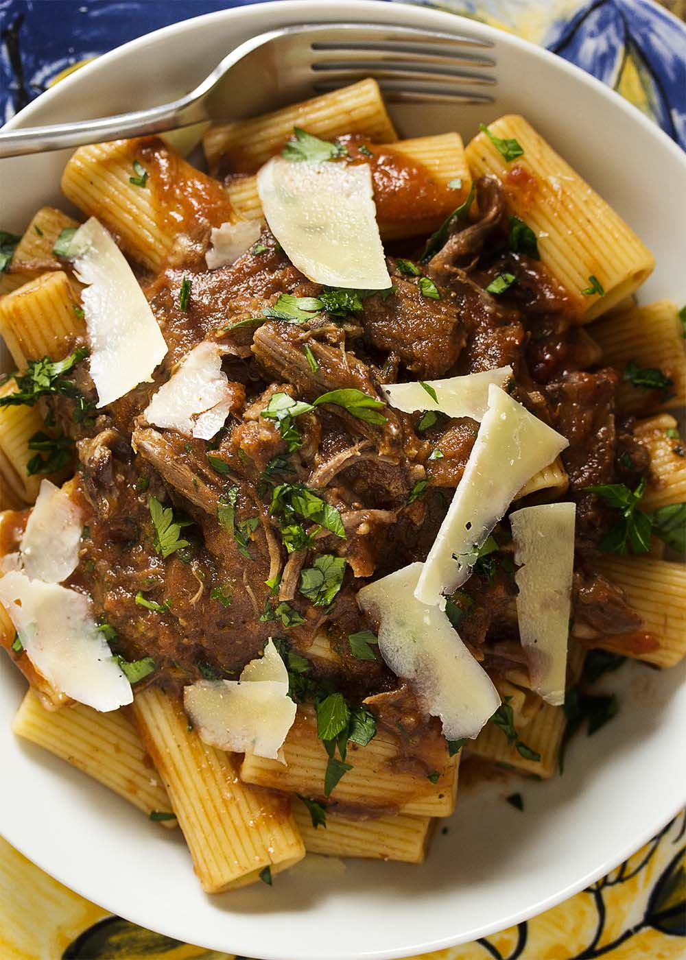 Top of view of shredded beef short ribs and rigatoni in a white bowl topped with shaved parmesan and parsley.