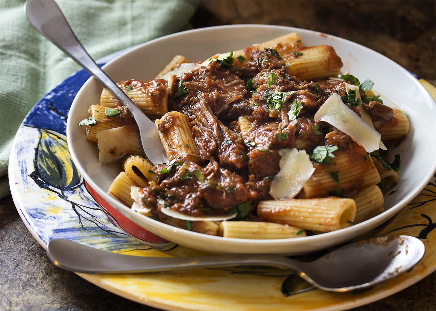 Close-up of a fork digging into a white bowl of short rib ragu and rigatoni.