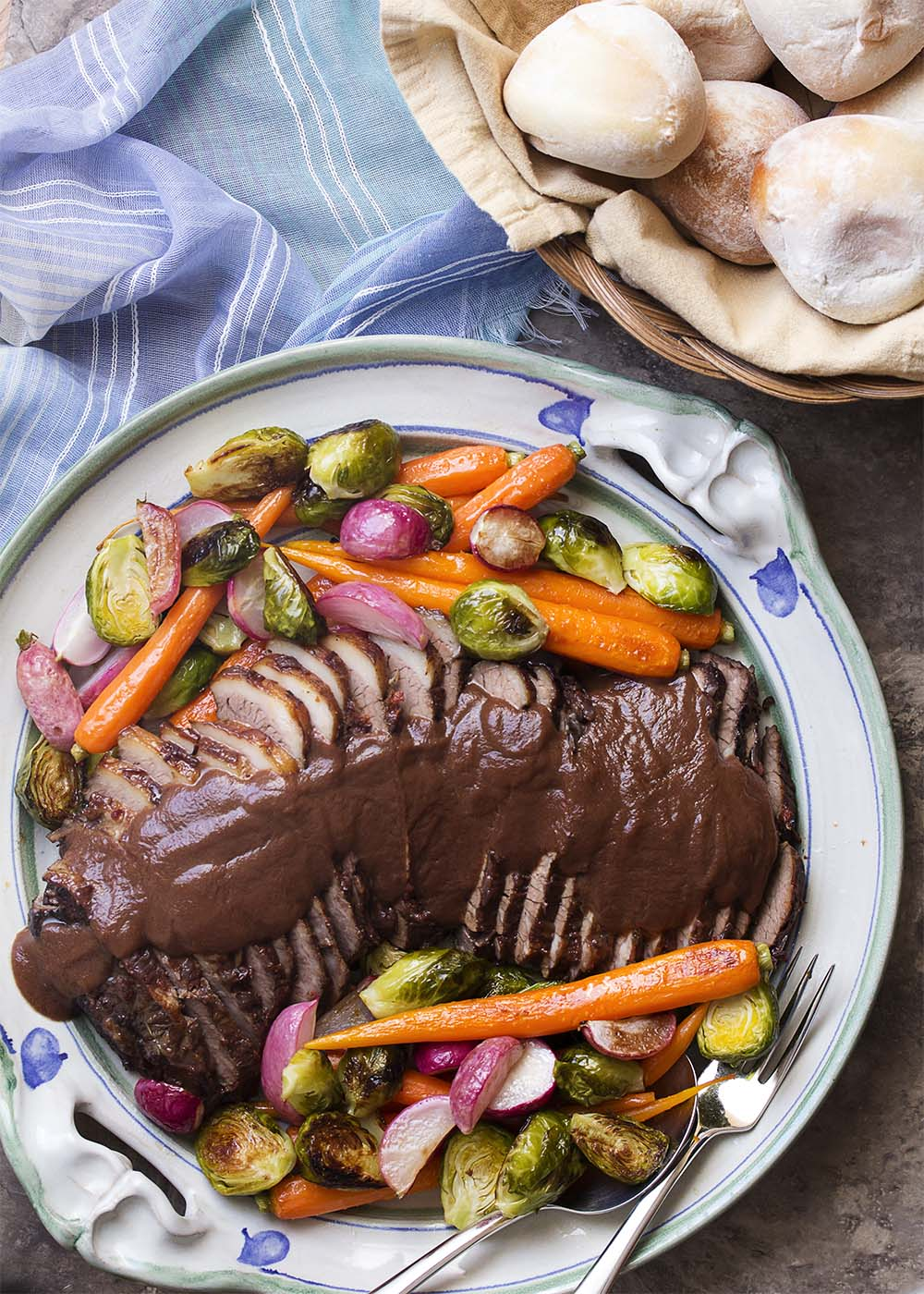 Large serving platter of sliced braised brisket covered with onion gravy and surounded by roasted vegetables.