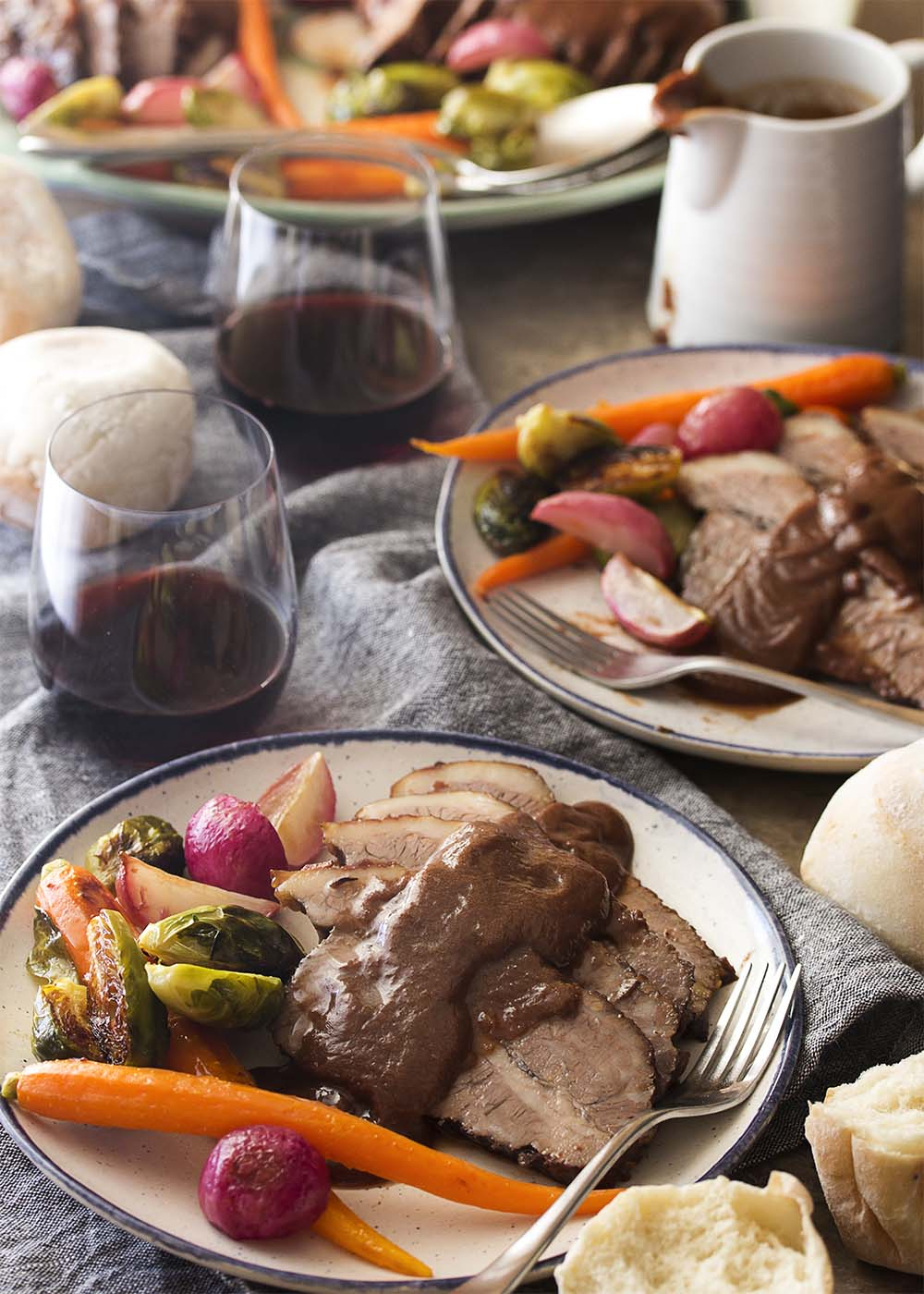 Table view of beef brisket on plates with vegetables alongside and gravy over the top.