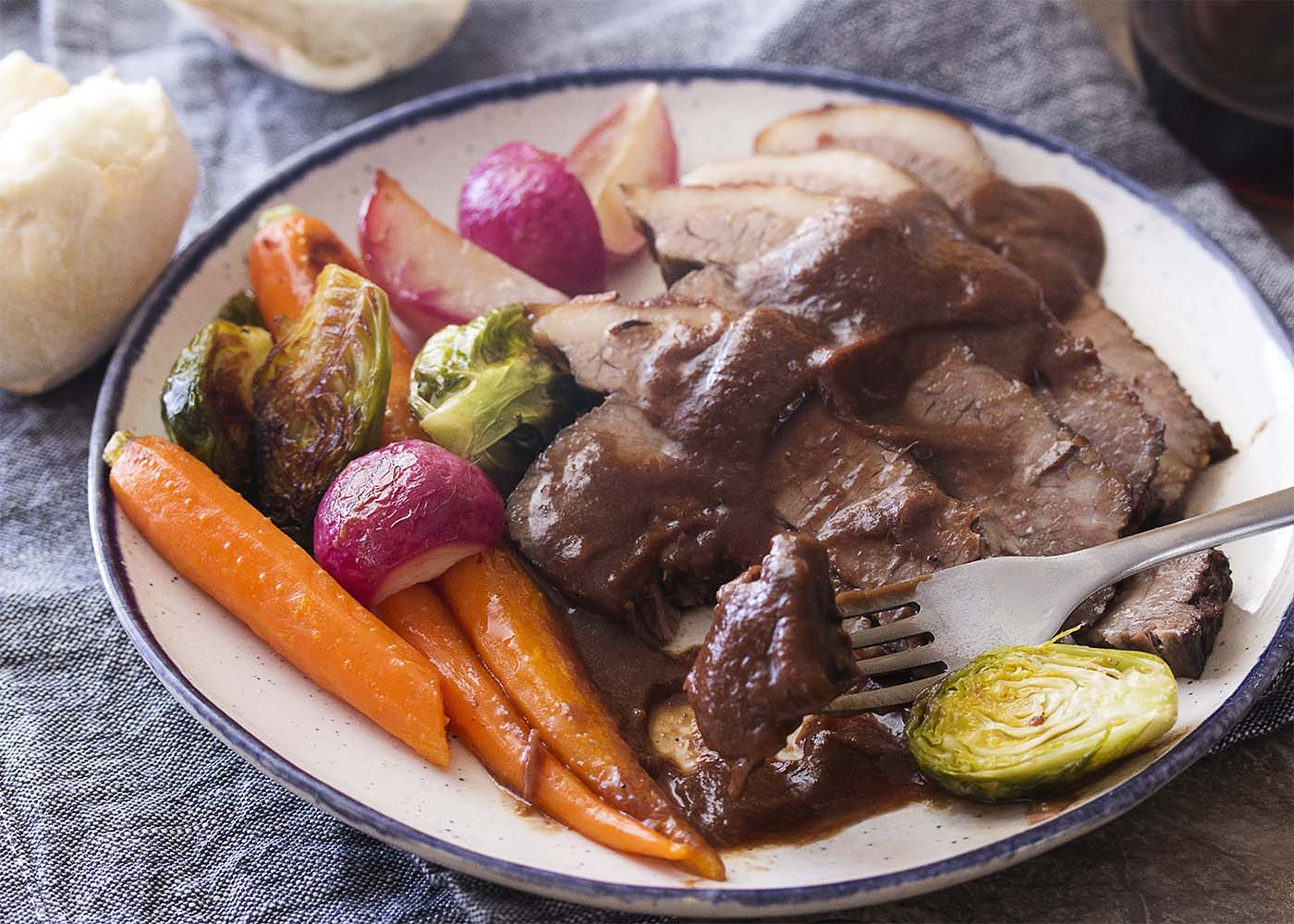 Closeup of a plate of beef brisket, vegetables, and gravy with a fork taking a piece of brisket.