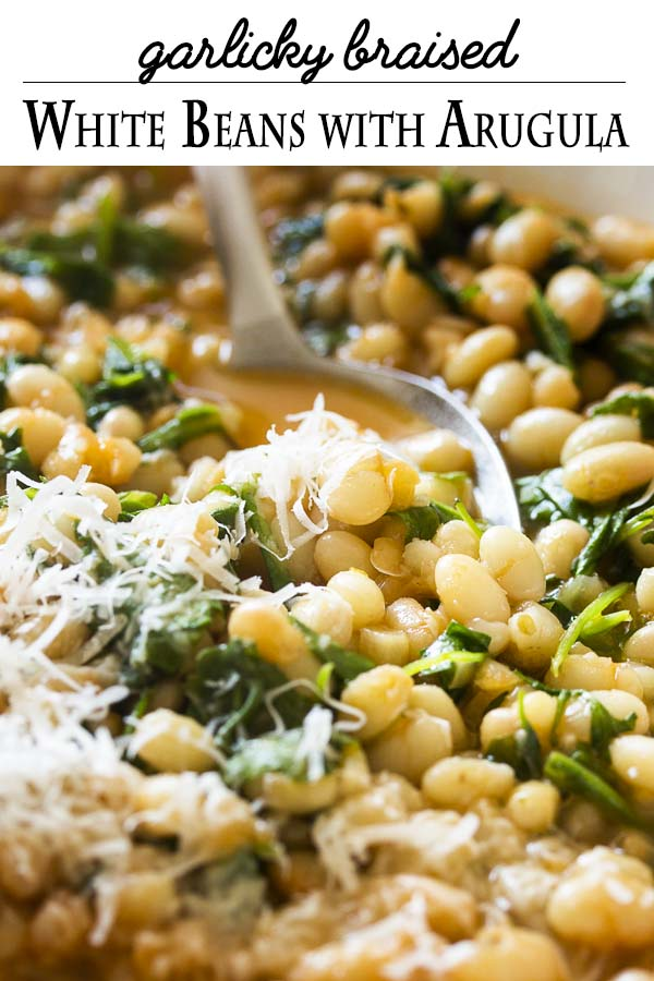 Arugula adds brightness and a peppery flavor to this simple and healthy recipe for Italian braised white beans with garlic and tomatoes. It's a satisfying side dish for all sorts of meals, especially grilled or seared lamb chops or steak.   justalittlebitofbacon.com #italianrecipes #sidedish #mediterraneandiet #beans #italianfood