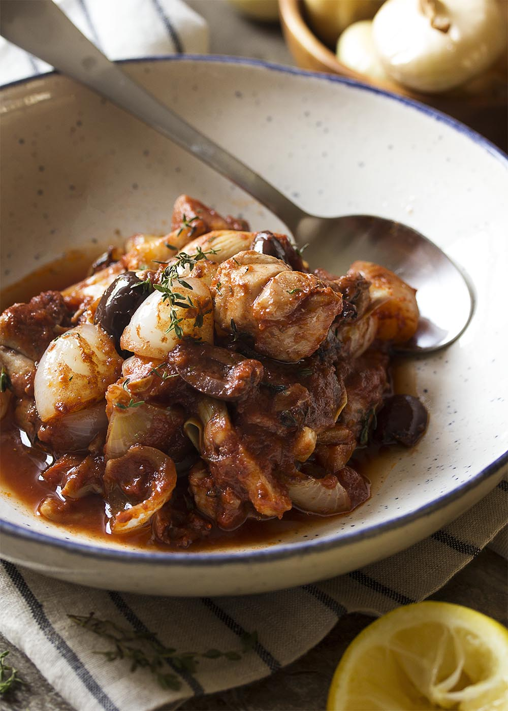 A bowl of chicken stifado showing the diced chicken, olives, onions, and artichokes all covered with a rich tomato sauce.