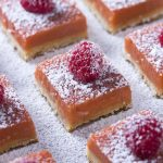 Homemade Meyer lemon raspberry bars are great twist on classic lemon bars! Start with a simple flaky and buttery shortbread crust and then top that with a thick and rich layer of lemon and raspberry curd. Tart, amazing, and a beautiful reddish-orange color.