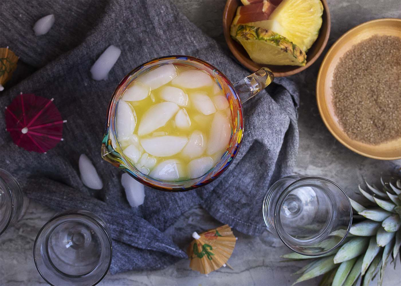 Top view of a pitcher of pineapple rum punch shown with glasses and garnishes.
