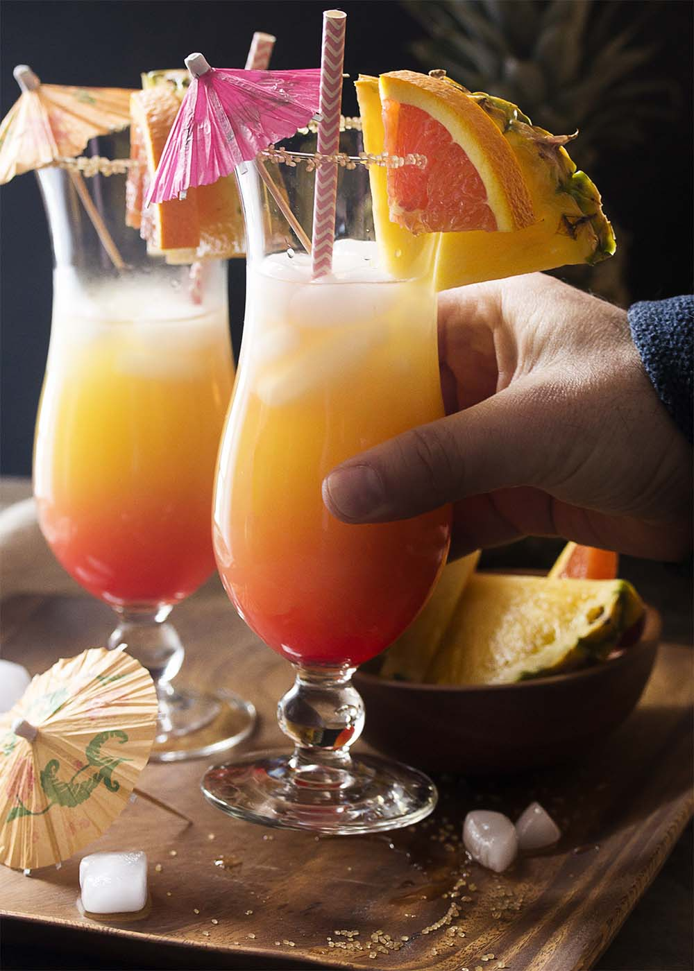 A hand taking a glass of the rum punch showing the layered sunset effect from the grenadine.
