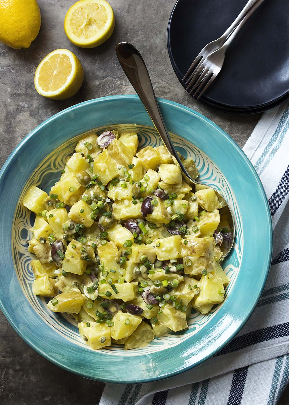 Top down view of potato salad in a blue serving bowl of diced yellow potatos, olives, and capers.