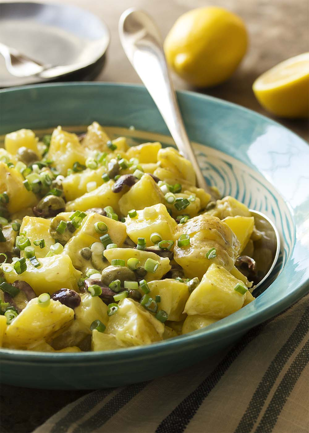 Side view of a blue serving dish of potato salad with olives and capers topped with scallions.