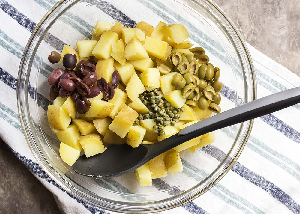 Glass mixing bowl showing the cooked potatoes, sliced black olives, sliced green olives, and capers.