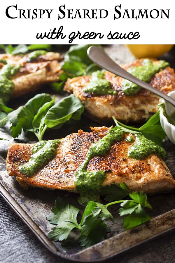 A simple pan searing in a cast iron pan gives my salmon with green sauce golden brown crispy skin worthy of a restaurant dinner! Add in an easy and vibrant sauce full of basil and parsley and you have a delicious and healthy weeknight meal. | justalittlebitofbacon.com #salmonrecipes #fishrecipes #glutenfreerecipes #dinnerrecipes #salmon