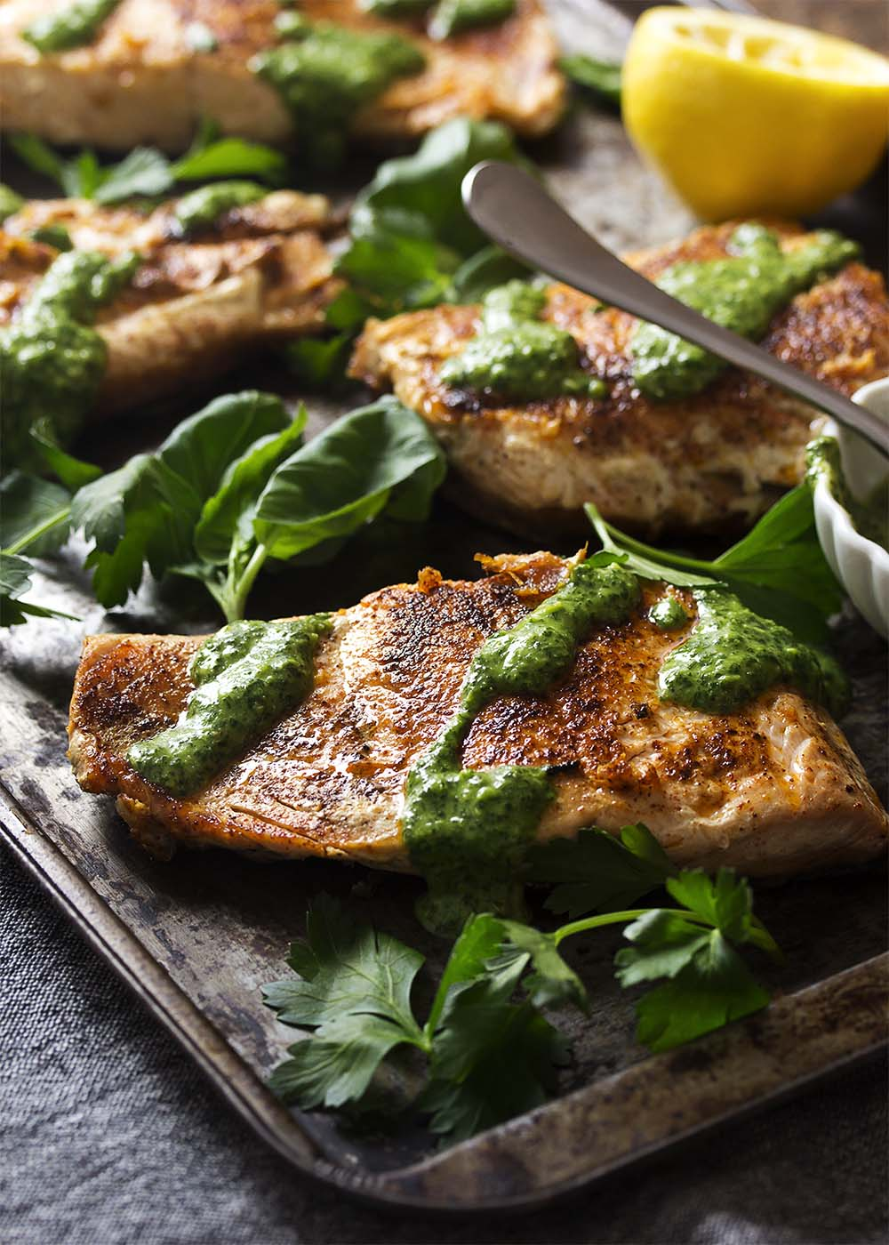 Golden brown salmon fillets on a tray drizzled with green sauce.
