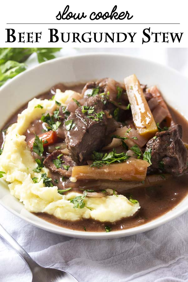 Grab a bottle of Burgundy or Pinot Noir because it's time to make some classic French comfort food! My recipe for slow cooker beef burgundy is wonderful to come home to after a long winter's day - tender beef, bacon, lots of onions, and carrots all in a rich red wine sauce. | justalittlebitofbacon.com #frenchfood #beefstew #slowcooker #crockpot #beefburgundy #frenchrecipes