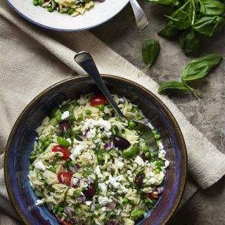 Greek orzo salad with peas, tomatoes, and feta is one of my favorite Mediterranean dishes to bring to potlucks, bbqs, and summer cookouts. It's a simple recipe, but always a hit.