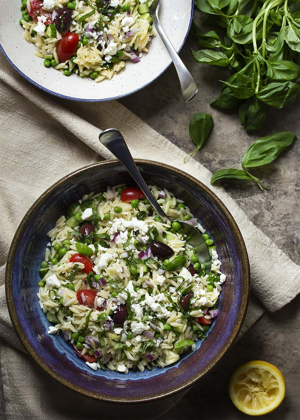 Top view of a big serving bowl full of Greek orzo salad