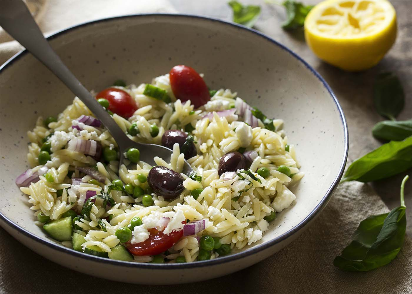 A wide bowl of orzo salad with a spoon all ready to take a bite.