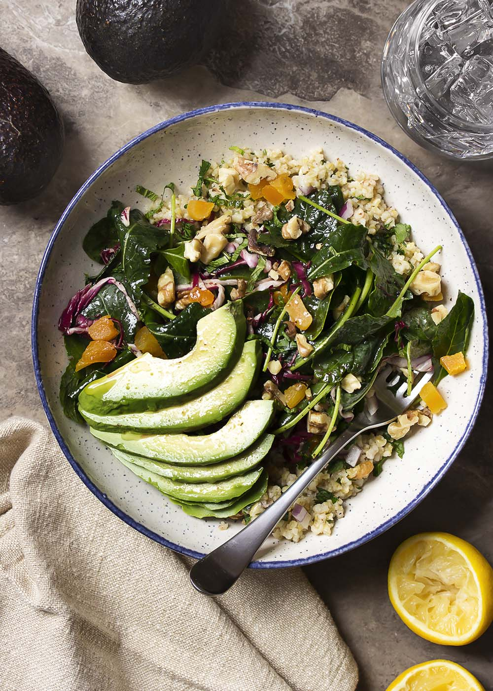 Top view of kale and freekeh salad buddha bowl topped with avocado, walnuts, and dried apricots.