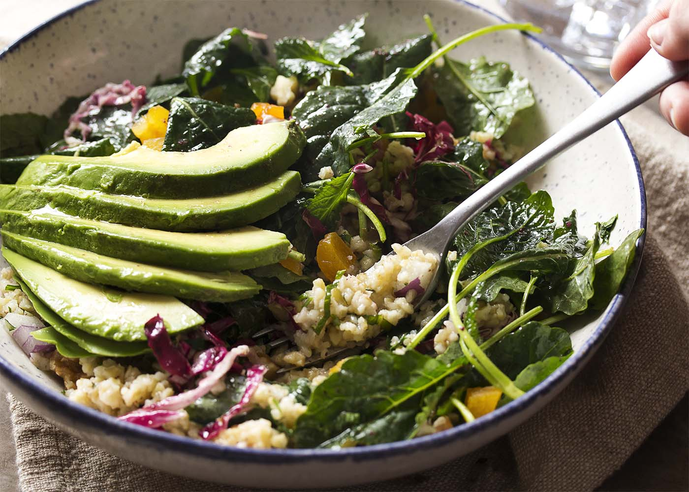Close up of a kale freekeh salad buddha bowl with a fork scooping out a bite.