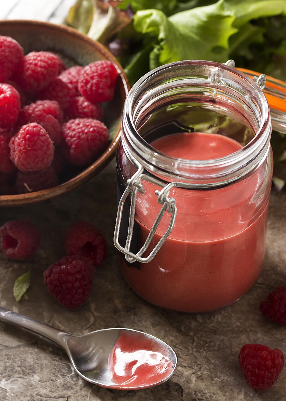A glass jar of raspberry vinaigrette with a bowl of fresh raspberries and spoonful of the dressing.