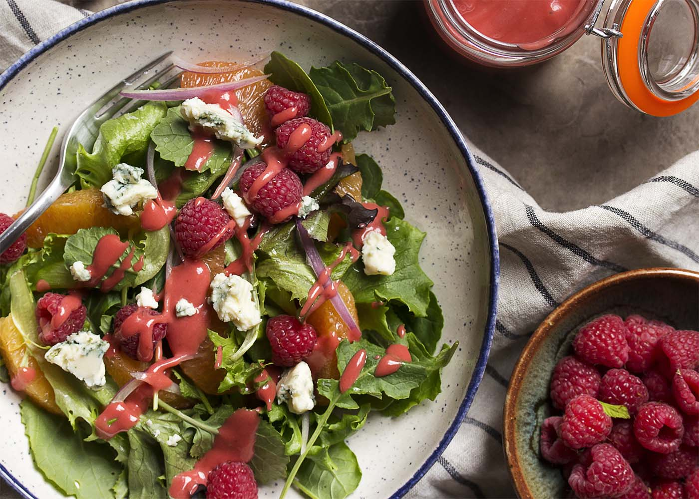 Overhead view of a wide bowl of a mixed greens, orange, and raspberry salad drizzled with raspberry vinaigrette.
